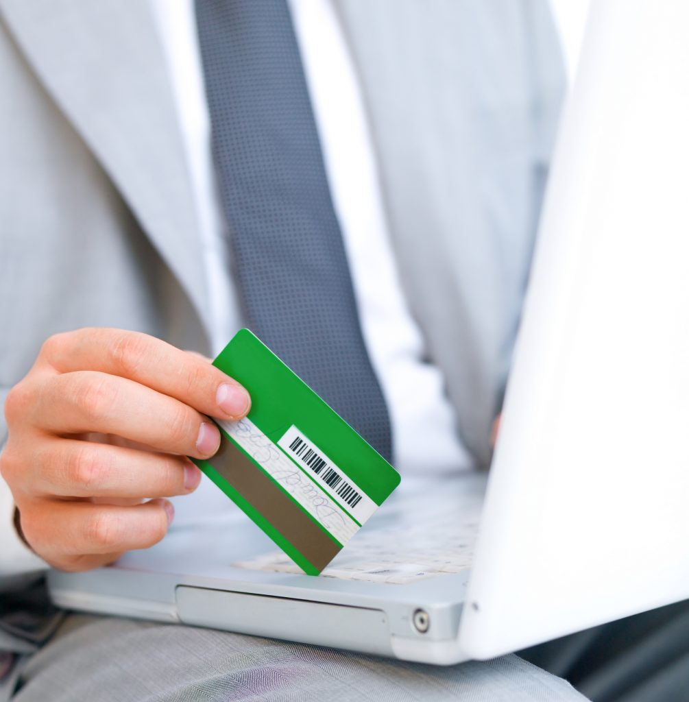 Business man with credit card sitting at computer