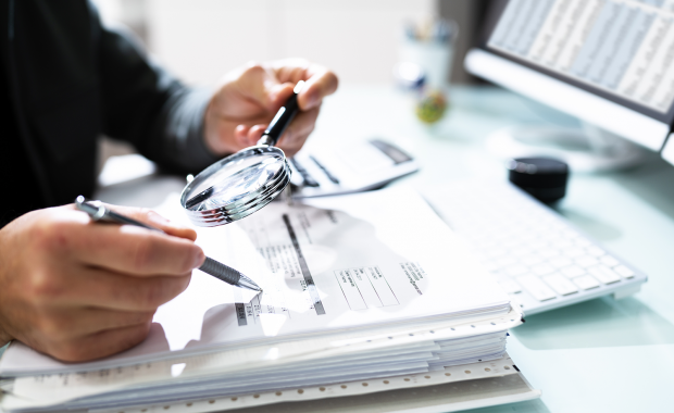 An individual holds a magnifying glass up to their expense data.